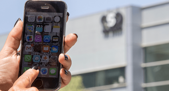 """) In this file photo taken on August 28, 2016, an Israeli woman uses her iPhone in front of the building housing the Israeli NSO group """"Pegasus"""", in Herzliya, near Tel Aviv. JACK GUEZ / AFP"""