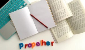 PropelHer banner including laptop, notebook and books