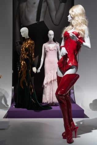 Installation view of the exhibition A Queer History of Fashion: From the Closet to the Catwalk featuring an ensemble worn by RuPaul, and evening gowns by Alexander McQueen (L) and John Galliano (R). Photograph © The Museum at FIT, New York.