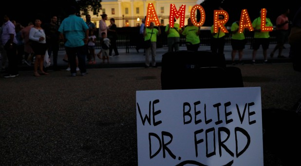 #KremlinAnnex protesters place a sign referring to Christine Blasey Ford, the woman who accused Supreme Court nominee Judge Brett Kavanaugh of a 1982 sexual assault, and spell out the word