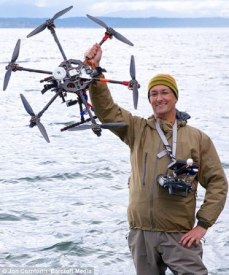 Photographer Jon Cornforth holding up and operating his remote controlled hexacopter which he used to take the snaps of Hawaii