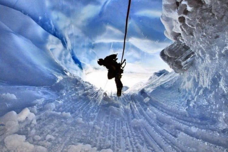 A hiker descends inside a moulin, Greenland