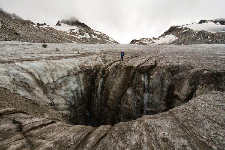 A hiker stands next to a massive moulin on Snowbird Glacier.
