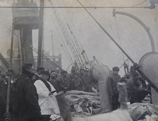 Priest praying over Titanic victims before they are buried at sea