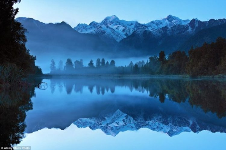 See Mount Tasman and Mount Cook perfectly reflected on the Lake Matheson near Fox Glacier in New Zealand