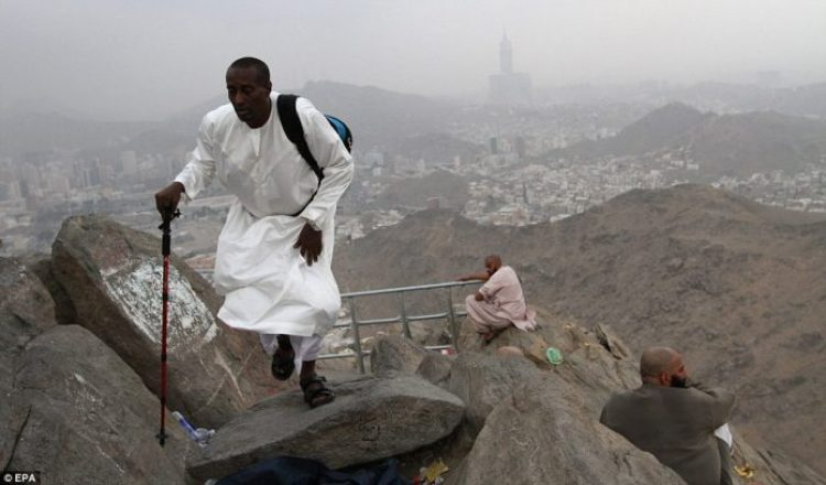 A devout Muslim pilgrim makes his way along the rocky path close to the top of Noor Mountain in Saudi Arabia