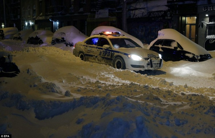 A New York Police Department car is seen driving past snow-covered cars on the Lower East Side of Manhattan during the large winter storm in the early hours of this morning