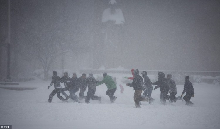 A group of bundled-up men play football in the snow in Downtown Brooklyn in New York on Saturday.