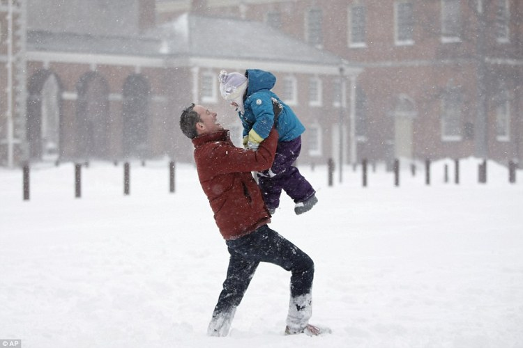 Dan Rafalin, left, lifts his daughter, Delila Rafalin, 5, while playing in heavy snowfall with their family on Independence Mall in Philadelphia
