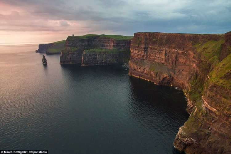 As the sunsets over the towering Cliffs of Moher in County Clare (above), Republic of Ireland, the pink light warms the craggy strata of the rockface