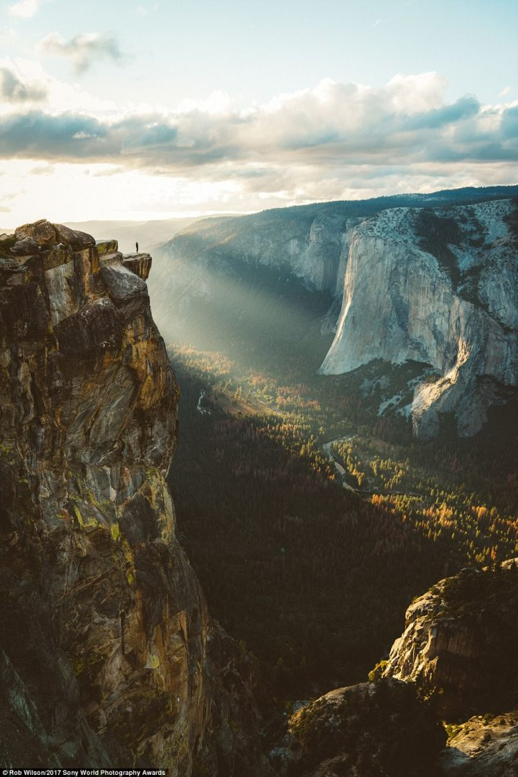 The sun setting over Yosemite Valley as shot from Taft Point while my girlfriend poses on the cliff edge during our road trip across the Americas