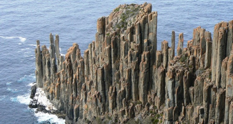 "The doleritic clifts surpass 100 m in topography above the sea along much of the southern and eastern coast of Tasmania, and some singular columns occur as giant ""totem poles"" standing in the sea."