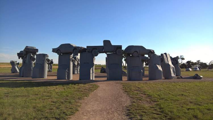 Carhenge arranged in a circle measuring about 29 meters in diameter, held upright in pits 1.5 meters deep, trunk end down, and arches have been formed by welding automobiles atop the supporting models.