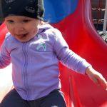 little girl on a slide, enjoying life