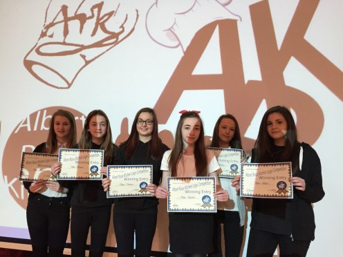 The girls show off their certificates in front of their logo designs at assembly