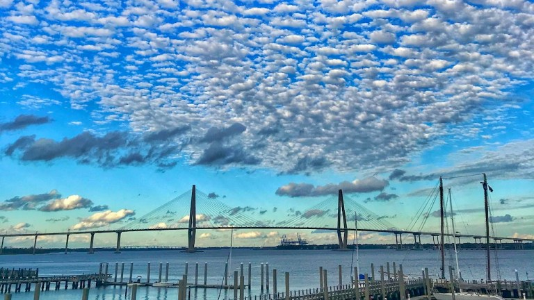 A view of Charleston Harbor from a marina, with the Ravenel Bridge behind and puffy clouds above