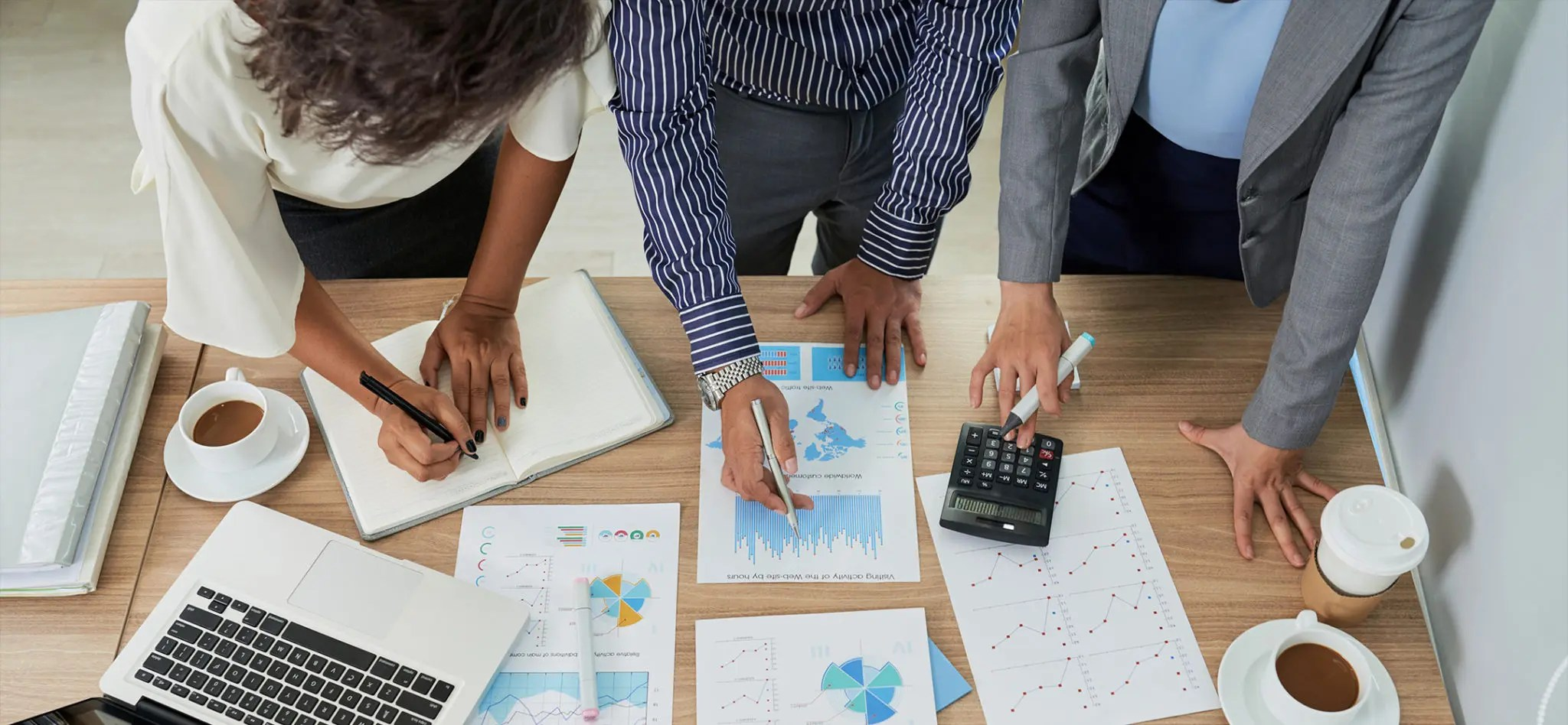 Three coworkers standing over a table analyzing charts and graphs during a meeting