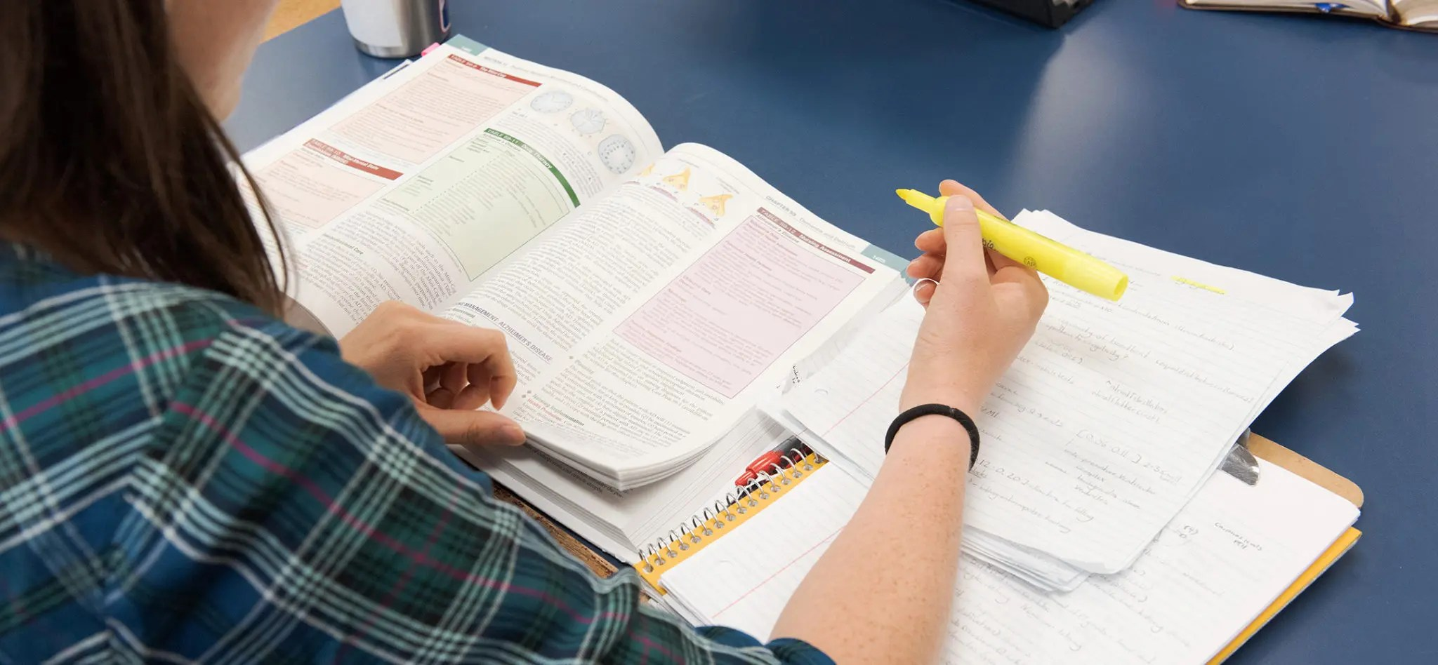 An over the shoulder view of a student looking at her book and notbook with a highlighter in her hand.