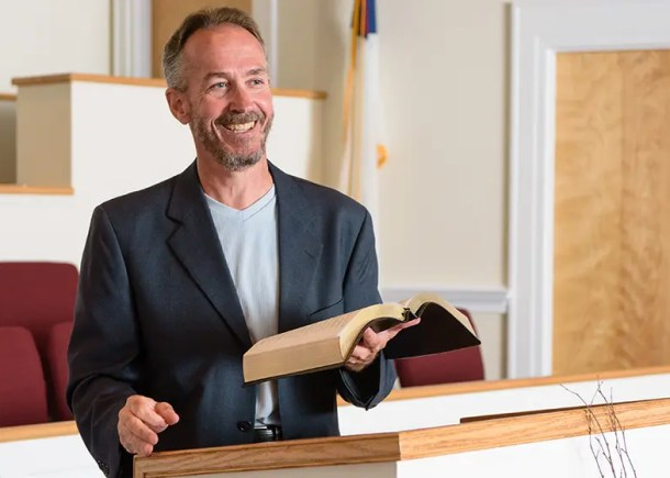 Professor Dr Peter Beck giving a sermon at a pulpit in a church.