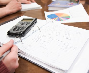 A students open notebook with accounting information written on the pages with a calculator and pie chart.
