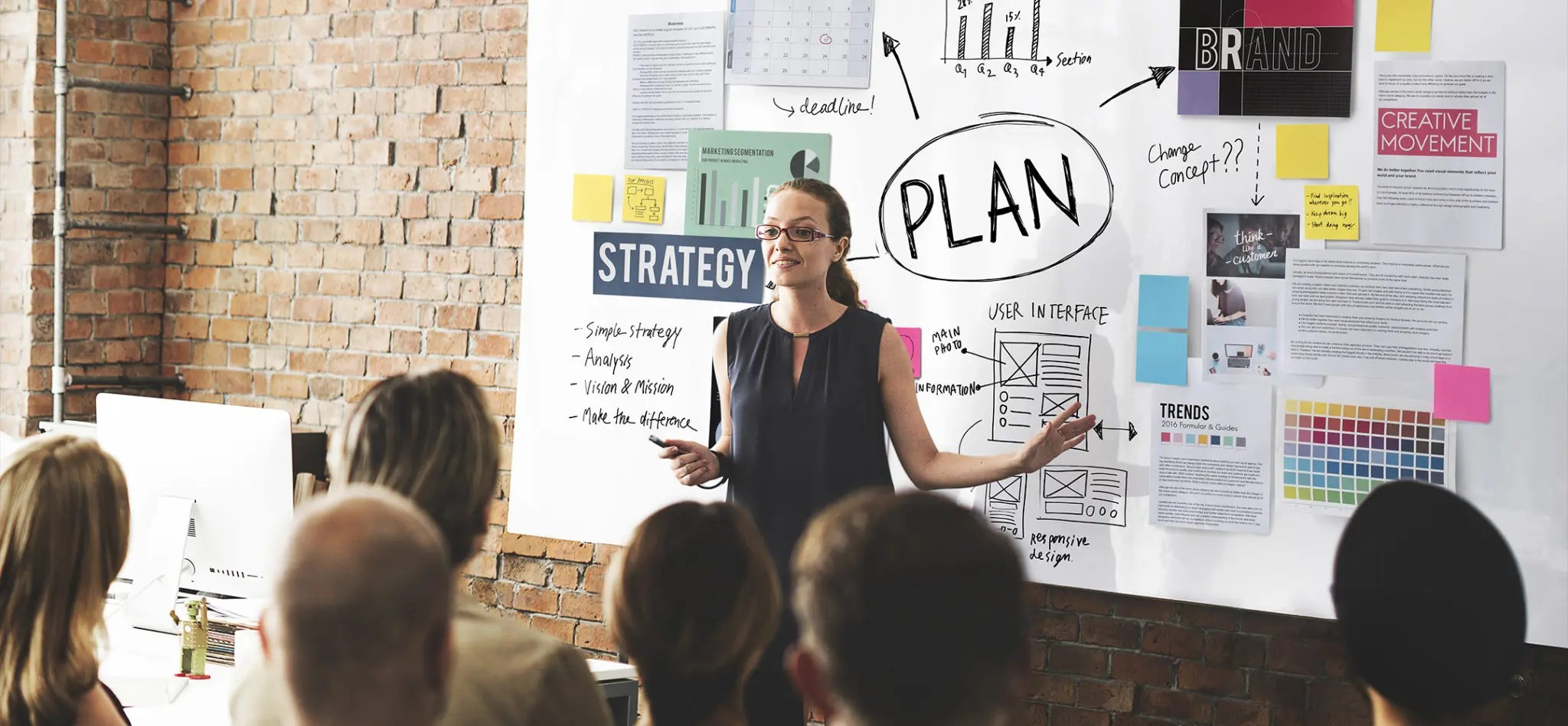A woman giving a marketing presentation on a white board to a group of employees.
