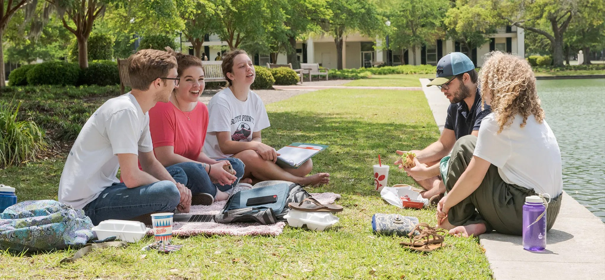 Students having lunch on the edge of the reflection pond.