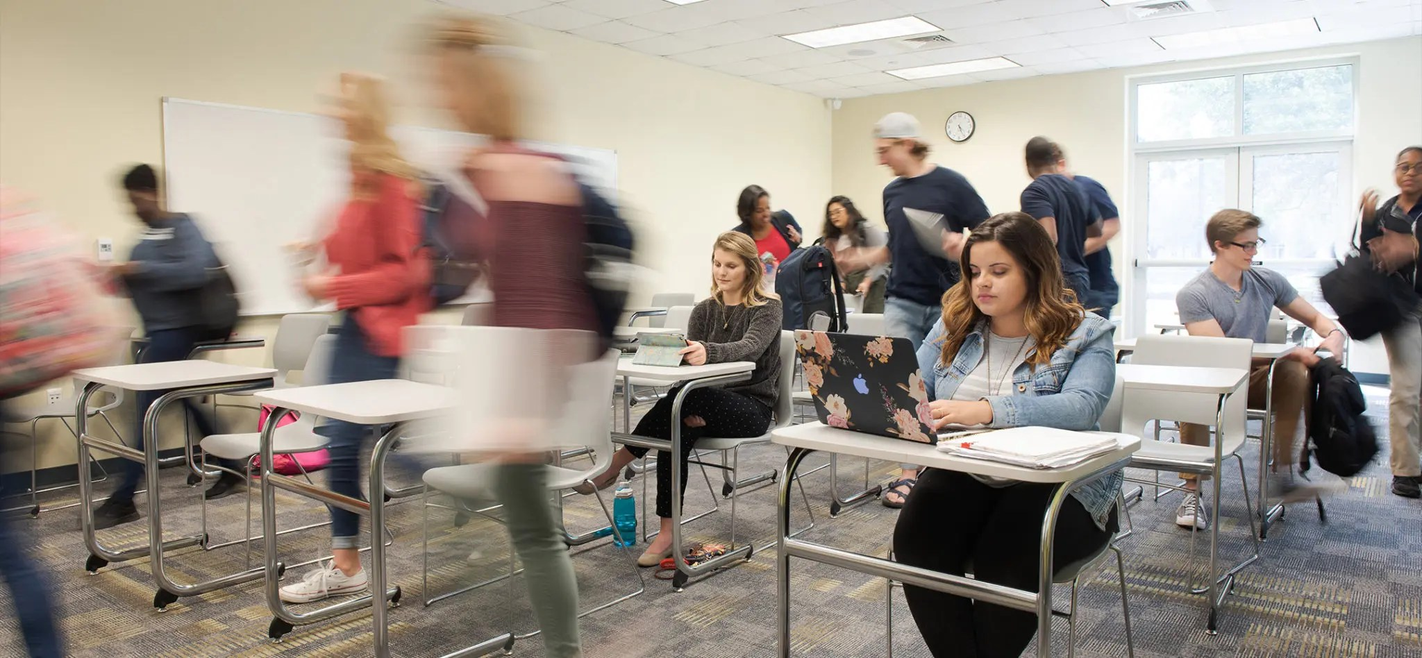Students in classroom with the effect of most students in motion leaving class.