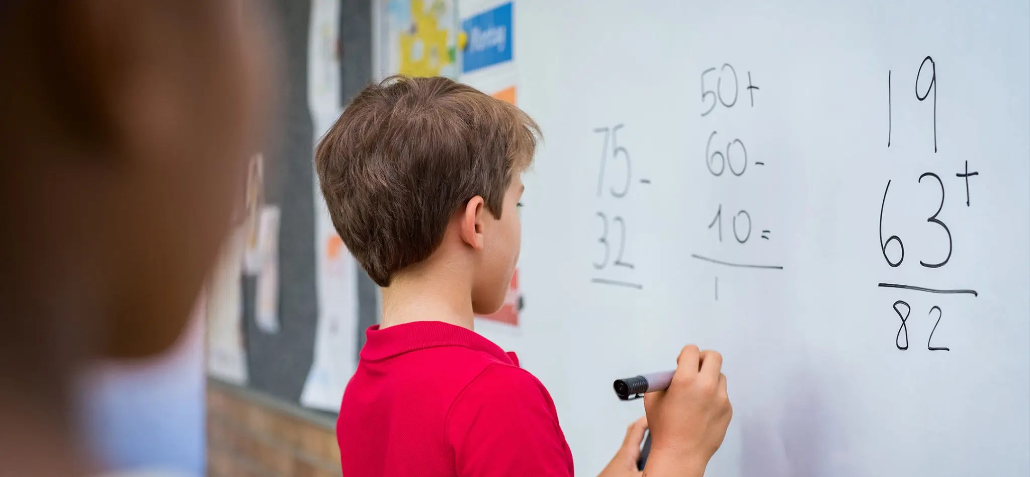 Rear view of young boy solving addition and subtraction on white board at school.