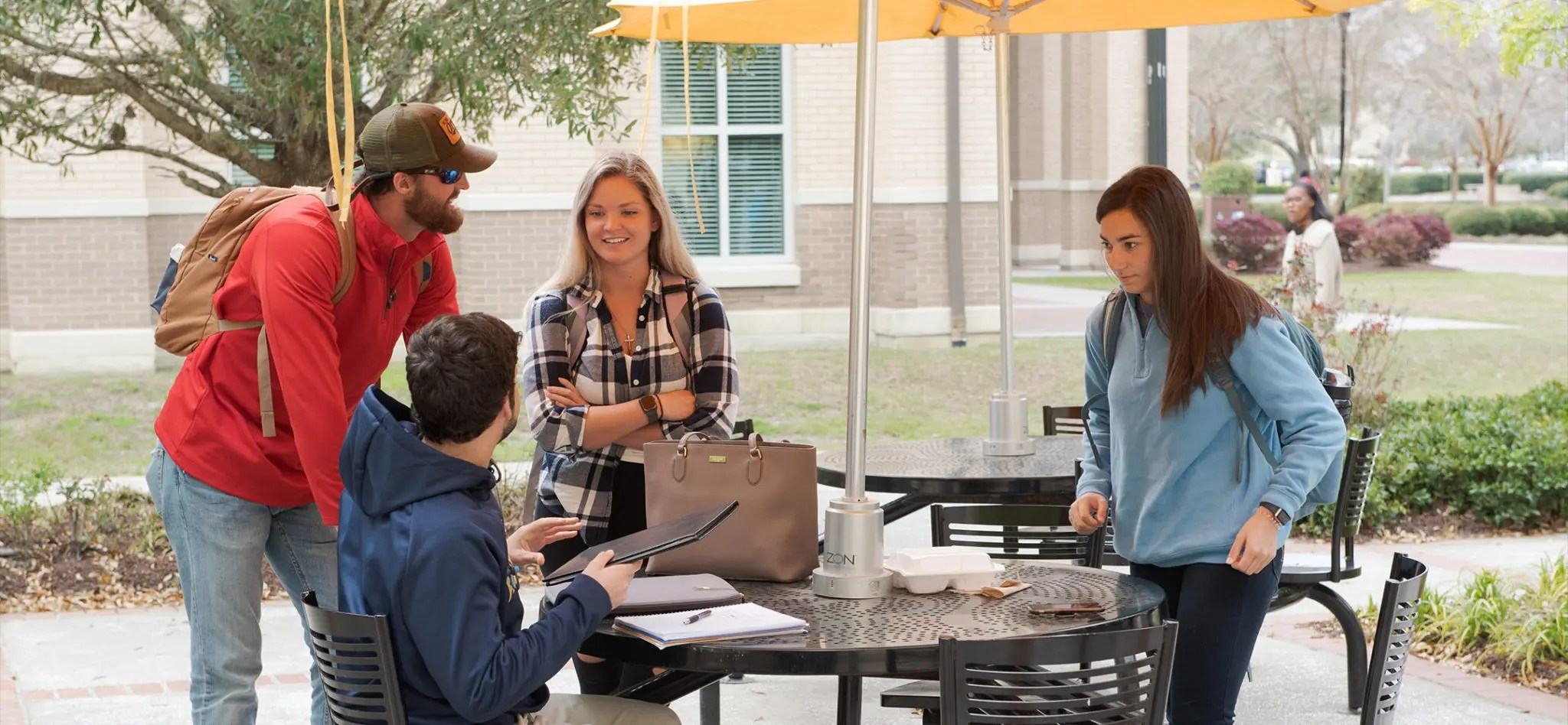 Four students on the CSU campus gathered around an outside table talking with each other.