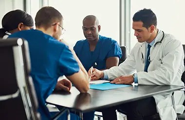 Young people on medical staff meeting with a man in a white coat showing something in a journal, sitting at table in bright room.