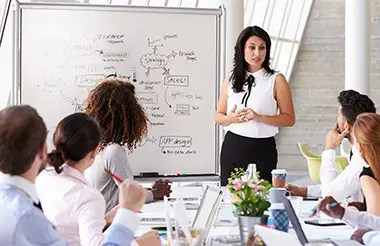 Hispanic business woman leading a strategy meeting at a boardroom table in a bright white office.