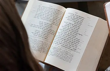 An open bible written in hebrew being held by a student.