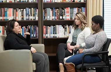 A counseling session between a counselor and two female students.