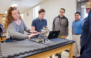 Students in an engineering lab looking at a computer controlled robot made of legos.