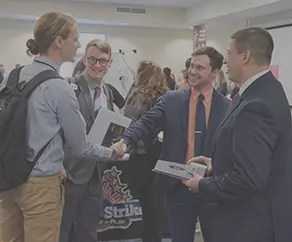 Four students dressed in business attire greeting each other and shaking hands in a career fair.