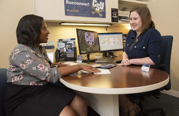 A student sitting down with an admissions counselor
