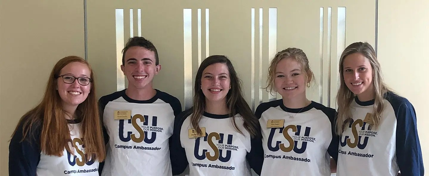campus ambassadors pose for a picture in front of csu logo in the christian leadership building.