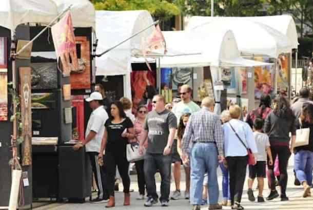 adults and children shopping for art at booths at lake norman festival of the arts