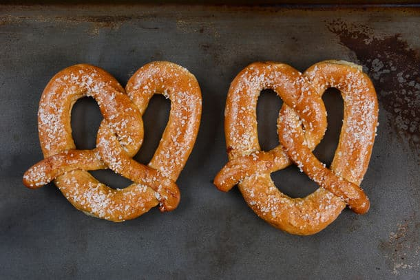 Two Large Sourdough Pretzels On A Metal Baking Sheet The Salted Snacks Are Side By Side In Horizontal Format