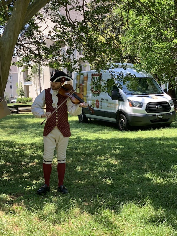 fiddler in colonial costume in front of olde mecklenburg brewery truck on Meck Dec Day at Charlotte Museum of History