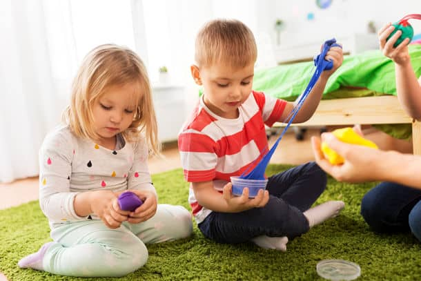 Childhood Leisure And People Concept Children Playing With Modelling Clay Or Slimes At Home Children With Modelling Clay Or Slimes At Home