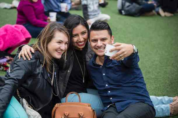three friends watching a concert, taking a selfie