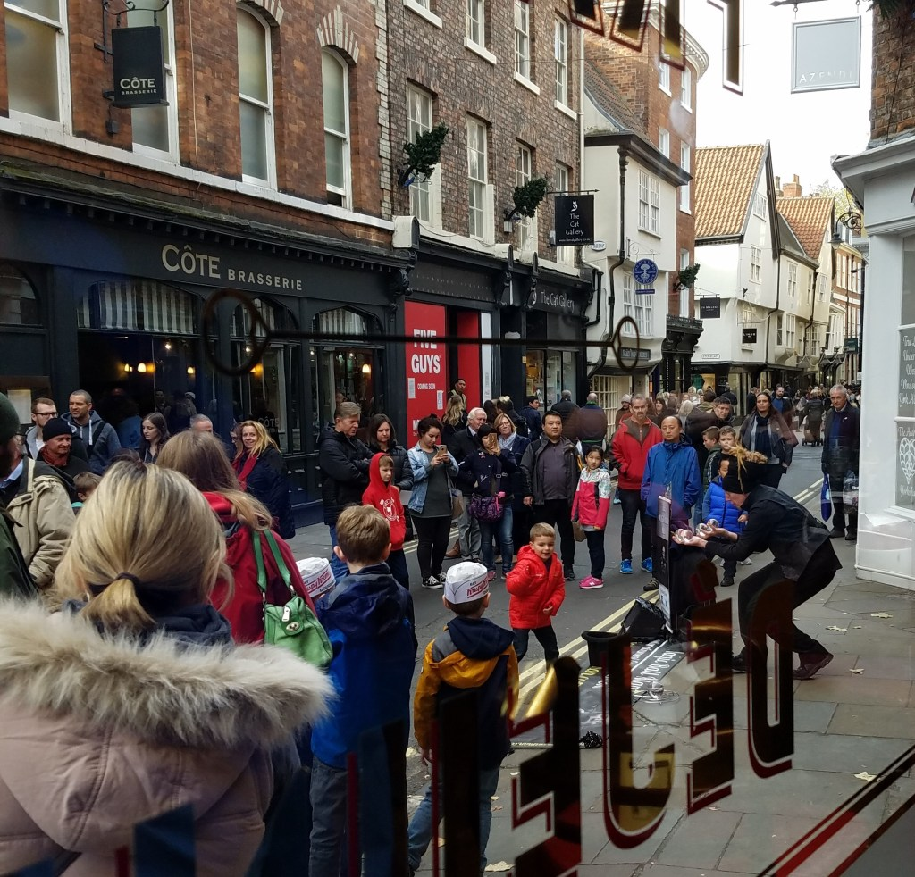 Watching a street entertainer through the window of Cafe Rouge at 52 Lower Petergate, in York, England.