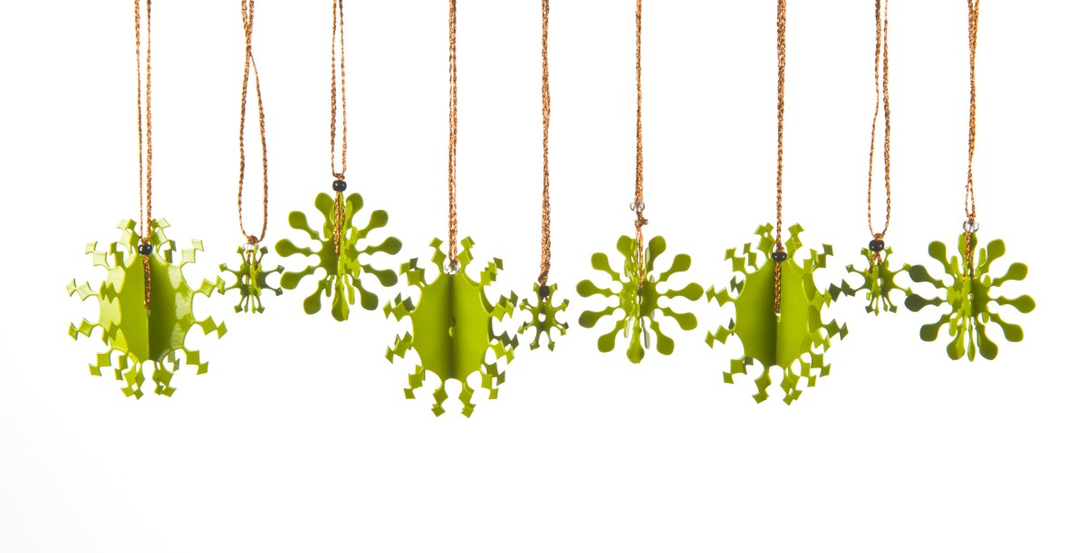 A collection of 3D metal snowflakes, some small, some medium and some large, coated in green enamel paint each with a copper thread for hanging on the Christmas tree.