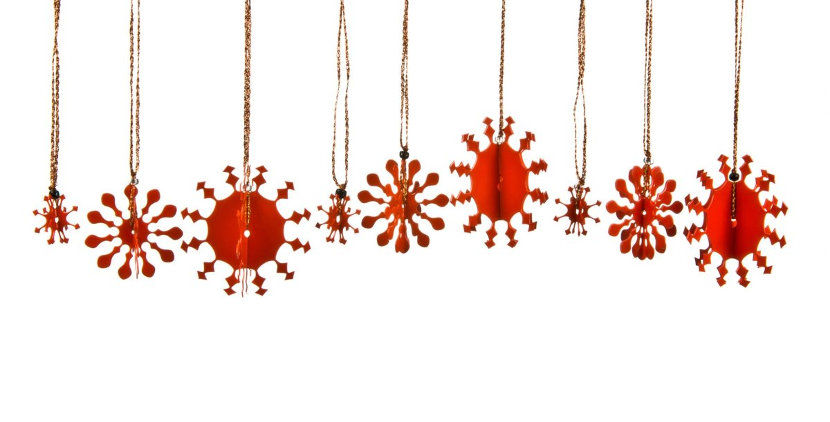 A collection of 3D metal snowflakes, some small, some medium and some large, coated in red enamel paint each with a copper thread for hanging on the Christmas tree.