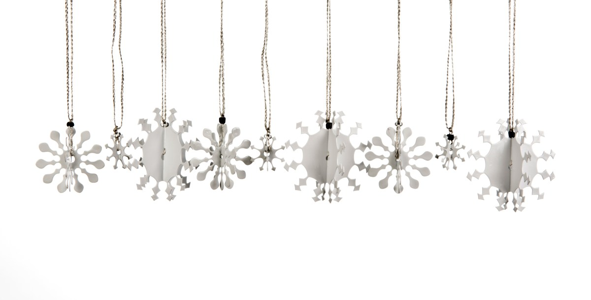 A collection of 3D metal snowflakes, some small, some medium and some large, coated in white enamel paint each with a silver thread for hanging on the Christmas tree.