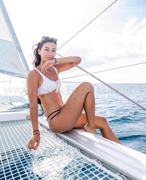 Menina em um biquini velejando ligado um viga em um catamaran lagoon 380 de CharterAlia em ibiza