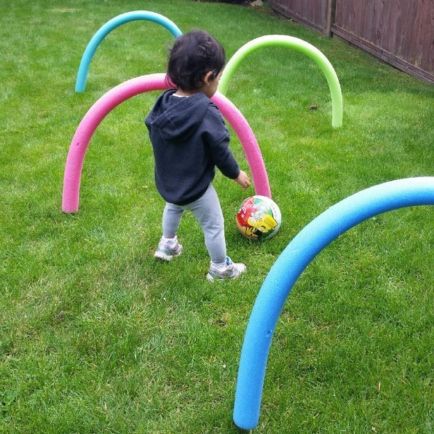 Pool noodles stuck in a lawn with a toddler playing soccer.