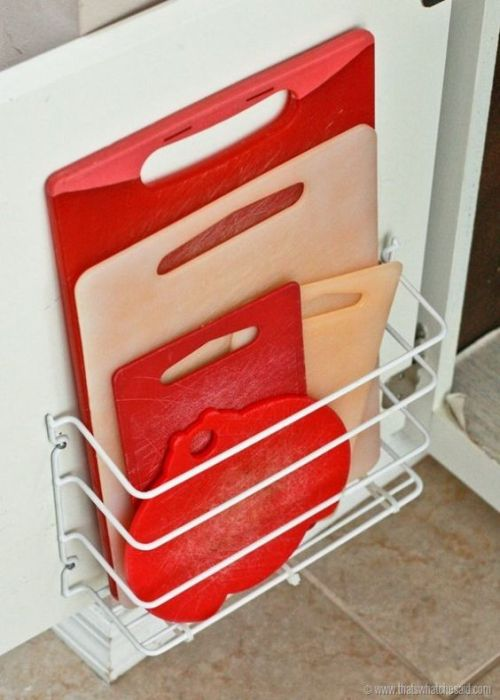 Cutting boards stored in a wire basket attached to a cabinet door.