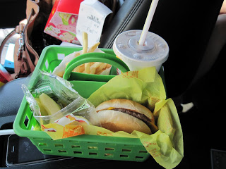 A green plastic bin holding food in a car